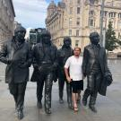 Gonzales stands among four metal statues of The Beatles on a London street.